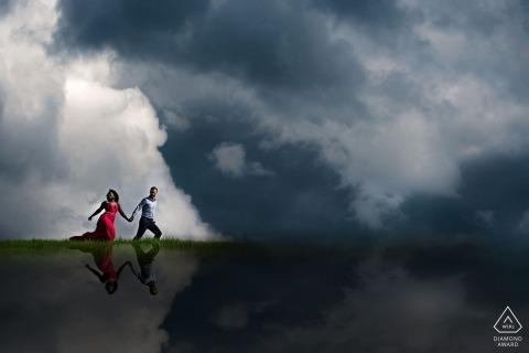 Couple courant dans les nuages au-dessus d'Edmonton, en Alberta, lors d'une séance de portrait de fiançailles.