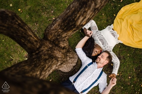 Edmonton, Alberta Engagement Portraits | Couple lying on the ground under a tree
