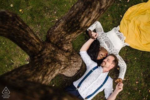 Edmonton, Alberta Retratos de compromiso | Pareja tumbada en el suelo debajo de un árbol