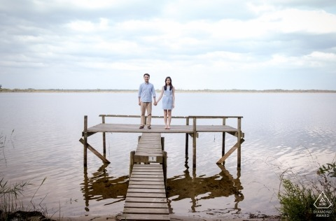A couple on a pier looking at the camera during engagement portrait shoot at Lacanau, south west of France