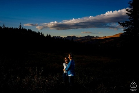 Engagement Portrait from Vail, CO   The Gore Range at Sunset with the couple looking into the light.