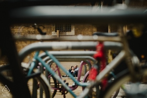 Engagement Photos from Barcelona - Image contains: sitting couple, parked bikes, light, depth of field