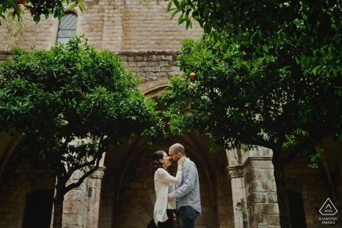 Zaręczynowy fotograf dla Barcelony - Obraz zawiera: parę, drzewa, łuk, budynek, pocałunek