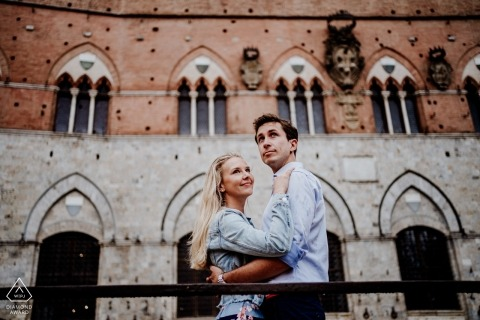 Verlobungsfotograf für Siena, Piazza del Campo - Porträt enthält: Paar, Umarmung, öffentlicher Platz, Gebäude