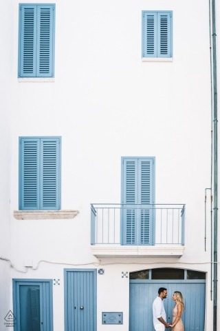 Engagement Photographer for Apulia - Portrait contains: couple, white, blue, building, apartment, doors, shutters, windows