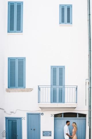 Fotógrafo de compromiso para Apulia: el retrato contiene: pareja, blanco, azul, edificio, apartamento, puertas, persianas, ventanas