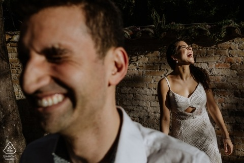 Engagement Photography for O Butia - Porto Alegre - Rio Grande do Sul - Image contains: laughing, portrait, brick, wall, couple