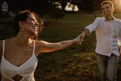Retrato de compromiso de O Butia - Porto Alegre - Rio Grande do Sul - La fotografía contiene: pareja, manos, hierba, árboles, parque, risas