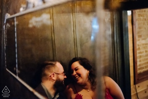 Engagement Photos from Texas | Couple snuggle and laugh in mirror reflection at Dean's Downtown cozy bar in Houston