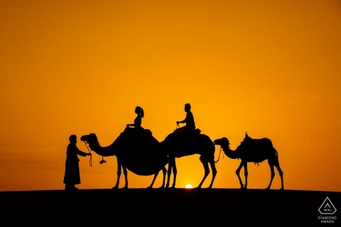 Engagement Portrait from Morocco Sahara Desert  - Image contains: camels, couple, desert, sunset, silhouette