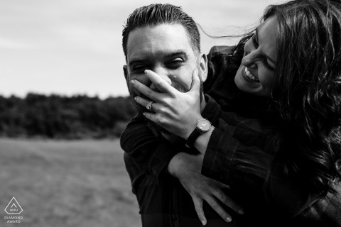 Engagement Photographer for Dover New Hampshire - She covers his mouth while riding piggy back in fits of laughter at their Dover NH Engagement Session