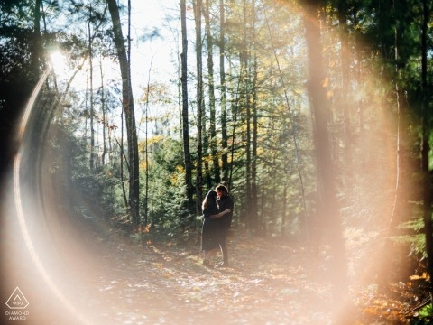Saco, ME Engagement Portraits on a Trail in the Trees - Photo with a Flare in the Fall