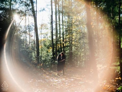 Saco, ME Portraits de fiançailles sur un sentier dans les arbres - Photo avec une fusée éclairante à l'automne