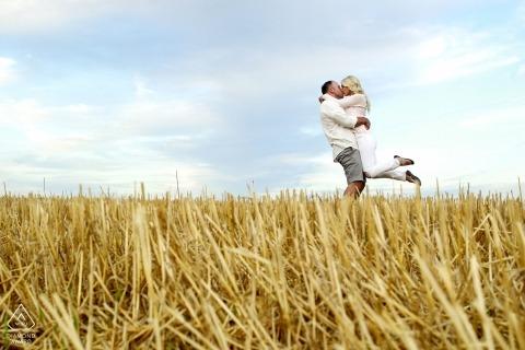 Elburn, IL | La pareja comprometida se abraza en medio de un campo de trigo cosechado.