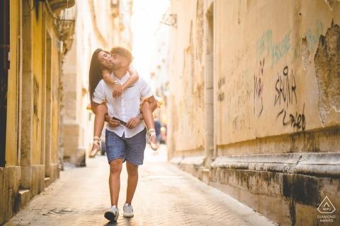 Pachino couple walking piggyback through the streets during prewedding portrait shoot
