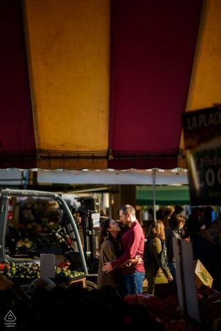 Jean-Talon Market in Montreal, Quebec engagement photo of couple embracing, framed by the farmer's market tents