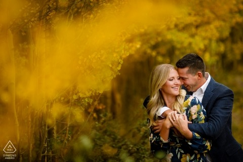 Breckenridge couple loving on each other in a grove of yellow aspen trees.