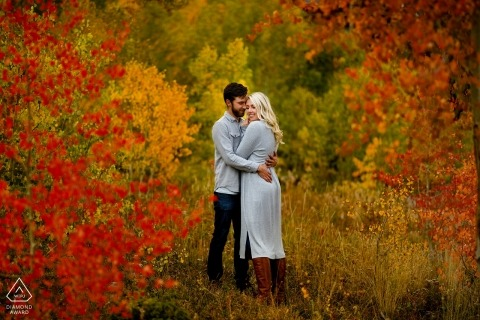Hugging his fiance in a grove of red, orange and yellow aspen trees in Silverthorne, Colorado.