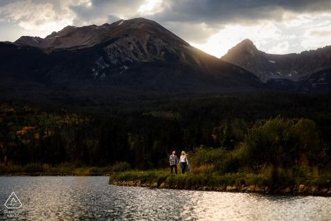 Silverthorne, CO photography engagement - Marcher au bord d'un étang alors que le soleil se couche sur la chaîne de montagnes Gore.