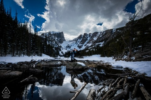 Estes Park Couple in the rockies during engagement session under clouds and blue skies