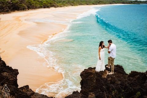 Makena, Maui Paar op een klif boven het strand tijdens verlovingsportret sessie op Hawaii