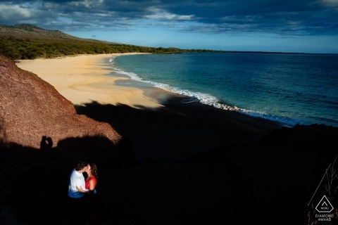 Verlobte Paare, die im harten Licht über dem Strand bei Wailea, Maui, Hawaii küssen