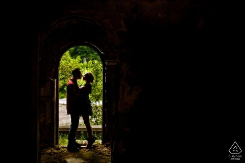 Seven Steps Canyon Brasov Engagement Photographer: Couple kissing in the door frame