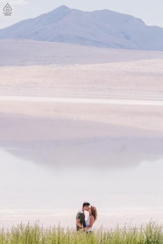 犹他州盐湖城订婚肖像会议期间,情侣在湖边接吻