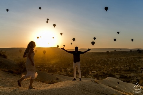 Cappadocia, Turkey Engagement Portrait Session | The girl running to the man at sunrise time and the hot air balloons and at the background