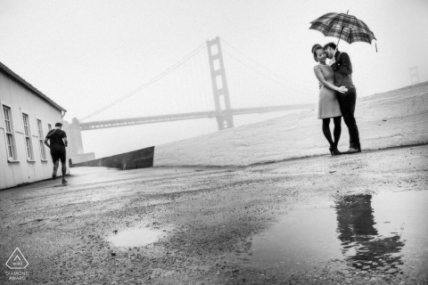 San Francisco Engagement and Wedding Photographer — Embrace in the rain. Couple with umbrella and puddles.
