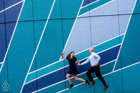 Crystal City, VA 	A couple jumps enthusiastically in front of a blue toned mural. Engagement photo session with fine art.