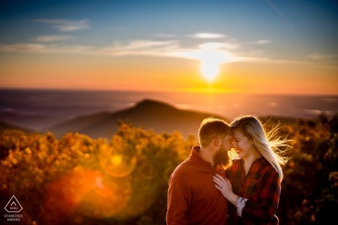 Engagement Photographer — A couple embraces each other after a lively sunrise hike up Hawksbill mountain in the Shenandoah National Park