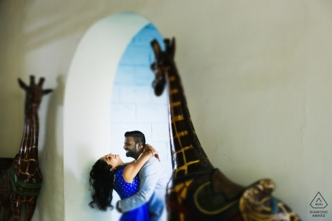 Miami engagement session with giraffe statues and arched doorway