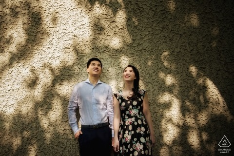 Shanghai engagement portrait against a wall with speckled sunlight and shadows.