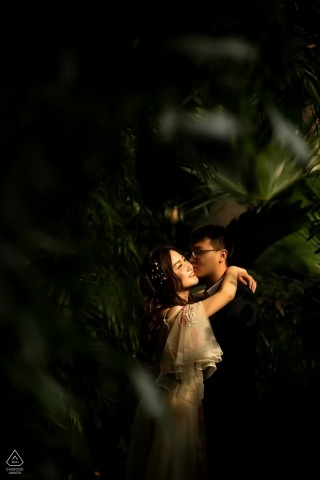 Panjin engagement portrait with green plants and in vertical.