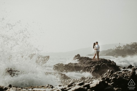 Malibu couple portrait at the beach with crashing waves on the rocks.
