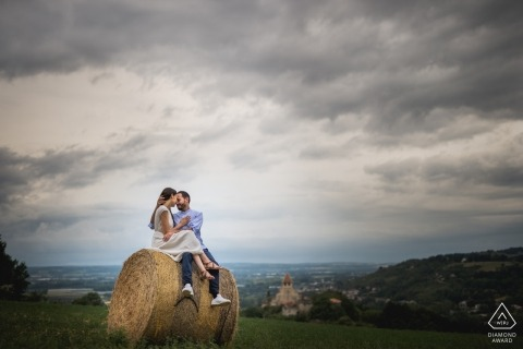 Agen, France couple portrait in the field sitting on a round hay bale.