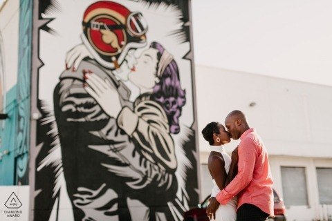 Engaged Couple kissing against giant mural in Wynwood, Miami, FL