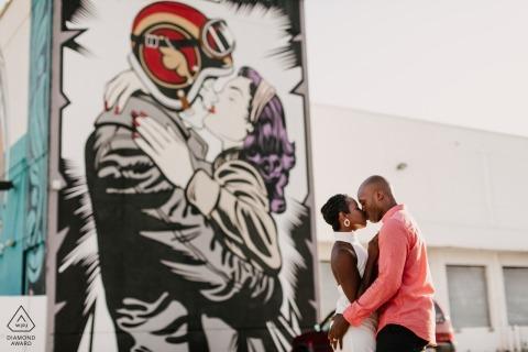Verloofd paar zoenen tegen gigantische muurschildering in Wynwood, Miami, FL