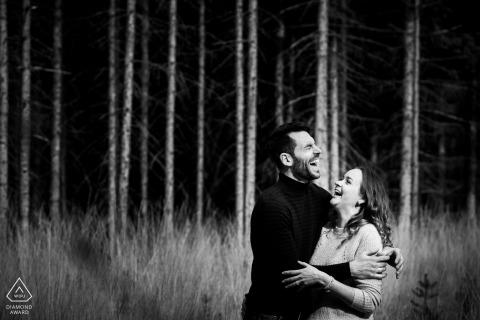 Landgoed-Höhle Treek-Paare, die Spaß während der Verlobungsfotozeit im Gras und in den Bäumen haben.