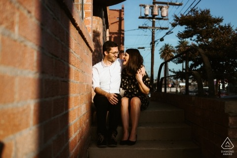 Downtown Los Angeles, CA Couple sitting on steps during afternoon engagement shoot.