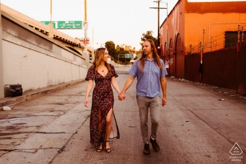 Couple wandering down alley at sunset in DTLA during engagement portrait session.