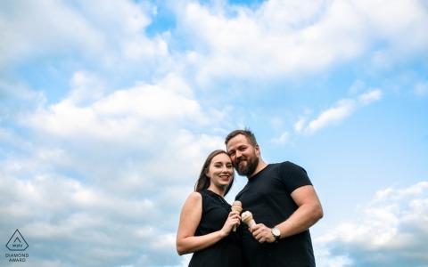 Verlobungssitzung Perths, Ontario - Paar isst eine Eiscreme unter dem blauen Himmel und den Wolken.