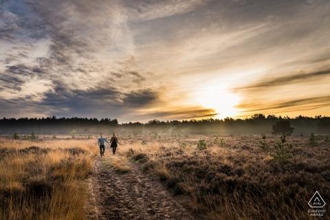Couple de fiancés marchant sur la lande lors d'une séance photo à Rucphense Heide, Rucphen