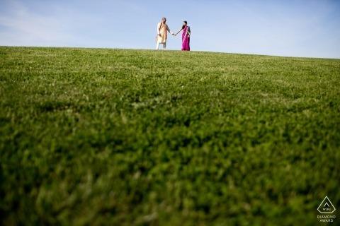 Paar bovenop een groene heuvel tijdens Boston, MA-sessie van verlovingsfotografie