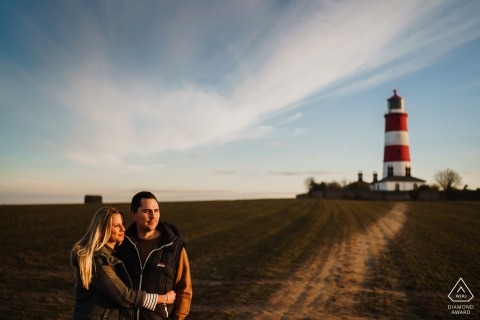 Sunset engagement Portrait | Un couple embrasse à l'extérieur du phare de Happisburgh, Norfolk, Royaume-Uni