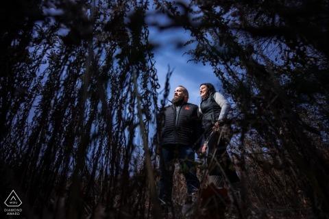 Sesja zaręczynowa w Minnesocie w Silverwood Park - para w wysokiej trawie z niebieskim niebem za nimi