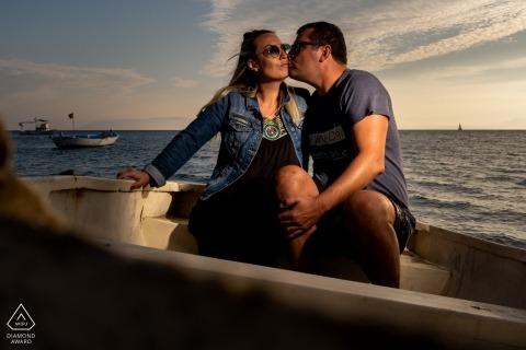 Badavut, Ayvalık, Balıkesir Couple sitting on a boat are kissing during engagement photo session.