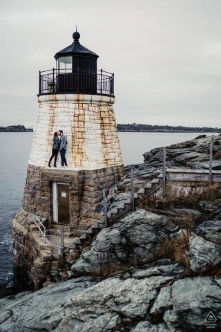 New England engagement portrait - Picture Session - Portrait contains: lighthouse, rocks, jetty, couple, water
