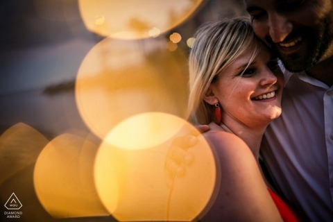 Cascais, PT Engagement Photo Session - Portrait contains: points, bokeh, light, hug, smile, red dress